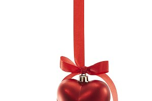 Christmas heart shaped decoration ball with red ribbon on white background