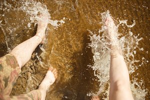 Couple legs splashing the sea water. Summer joy