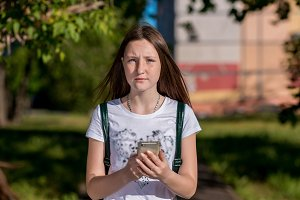 Girl Brunette Schoolgirl. In summer in the city in nature. In his hands holds a smartphone. The concept of a call to parents. Emotionally looks into the frame. He rest after school.