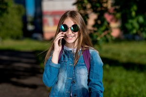 Girl schoolgirl. Summer in nature. In hands holding a smartphone communicates over phone. Smiles happily. In sunglasses and a denim jacket. Emotions of joy and pleasure. The concept of positive life.