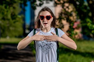 Beautiful schoolgirl girl. Summer nature after school. Glasses, heart is shaped. Smiles happily. Gestures of hands are held by heart. The concept breath surprises surprise. Emotion of enjoying gift.