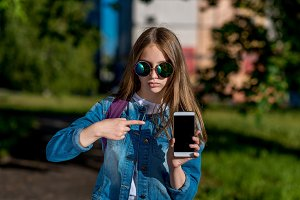 Little girl schoolgirl in sunglasses. Summer in nature. In his hands holds a smartphone. A finger points to phone. The concept is a new gadget app. Emotion focus concentration.