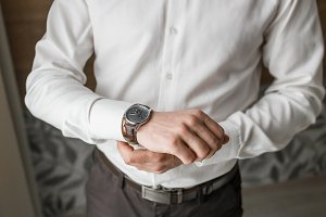 Businessman or groom checking time from watches
