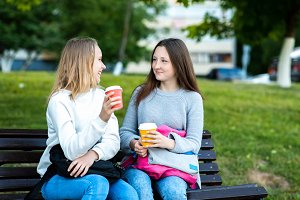 Two teenage girls are schoolgirls. In summer in the park on the street. Holds hands with cups of coffee or tea. He talks happily. The concept of school friends. Emotions of joy and happiness.