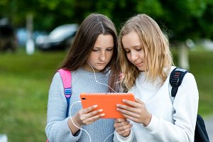 Two teenage girls. In summer in park after school. In hands holds tablet. He watches movie listening to music. The concept of friends best friends. Watching video on Internet social networks.