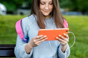 The girl is a teenager. Summer on the bench after school. In her hands holds a tablet. He watches movie listening music. The concept outdoor recreation. Watching video on Internet social networks.