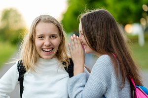 Two girls schoolgirl. In summer in park in nature. Teenagers communicate on street. Tell each other in ear. The concept of secret is a mystery. Emotion of happiness of joy, a joke of pleasure.