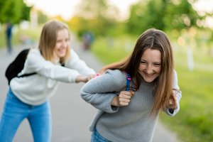 Two girls schoolgirl. Best girlfriends. In summer, the parks are in nature. Have fun on the street. The concept is best friends. Emotion Happiness is the joy of fun from the game After the lessons.