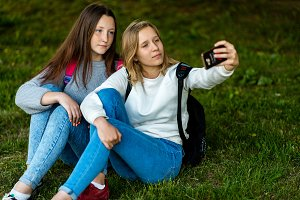 Two girl friends schoolgirl. Summer in park in nature. Sit on the grass, backpacks. In his hands holds a smartphone. Take photos on the phone. The concept is best friends. Emotion serious person.