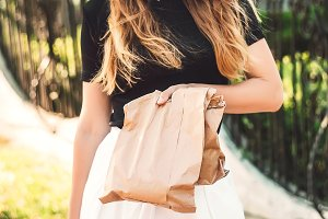 in the hands of the girl packages with a purchase. purchase. gift. surprise. Street style. Sun rays