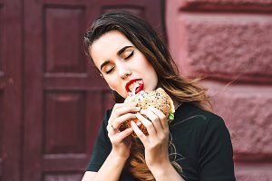 the girl is biting the burger. enjoys. a piece of food. Red lipstick. city Style. fast food.
