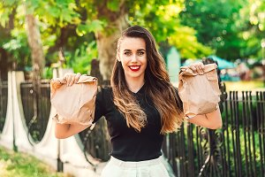 the girl holds two packages for sales. packages for eating. smile on his face. red lipstick on the lips. long hair