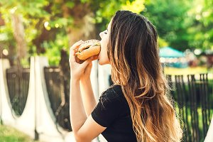 the girl is biting a hamburger. in a bun filling with meat. hearty high-calorie food.