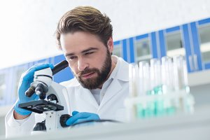 Professional bearded scientist looking into the microscope