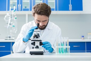 Smart confident scientist looking into the microscope