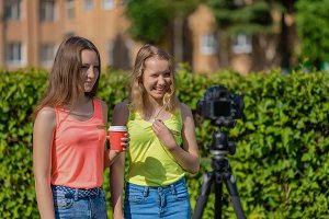 Two girls schoolgirl. Summer in the street. Smiles happily. Record vlog and blog subscribers. Record video lesson for Internet. Use camera with tripod.