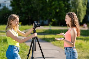 Female student. Summer in nature. The concept of the interview. Emotions of happiness are positive. Record vlog and blog subscribers. Record video lesson for Internet. Use camera with tripod.