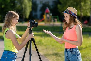 Two girl friends. Summer in nature. Friendly communication. Concepts of the interview. Record vlog and blog subscribers. Record video lesson for Internet. Use camera with tripod.