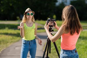 Two girl friends. Summer in nature. They broadcast on the Internet. Concepts of the interview. Record vlog and blog subscribers. Record video lesson for Internet. Use camera with tripod.