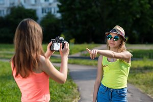 Two girl friends. Summer in nature. Records video. Schoolgirls on change make photos. Smiles happily. Concept you can.