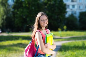 Girl schoolgirl. In summer after school. In the hands holds a notebook backpack. The concept of learning in nature. Emotion happy smiling.