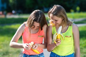 Two girl friends. Summer in nature. In hands of holding Bananas. The gestures of the hands clean the banana. The concept of eating in nature. Emotions happy smile.