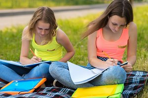 Two teenage girls. Summer in nature. Do lessons in notebooks. They sit on grass on striped blanket. Write assignment in notebook. The concept of school education in nature. Emotion serious training.