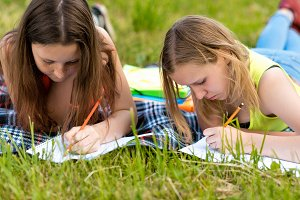 Two teenage girls. Summer in nature. Do the lessons in notebooks. They lay on grass on a striped blanket. Write the assignment in the notebook. The concept of school education in nature.