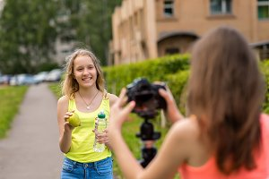 Two girl friends. Summer in nature. Record video on camera. The concept of young bloggers. Healthy eating. Emotions smile happily. In her hands holds a bottle of water and an apple.