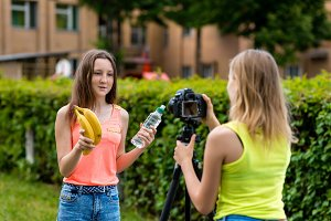 Two girl friends. Summer in nature. Record video on the camera. The concept of young bloggers. Healthy eating. Emotions are talking on the camera. In her hands holds a bottle of water and bananas.