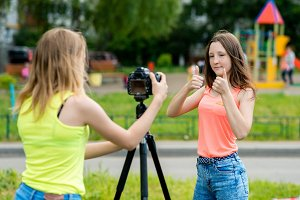 Two girl friends. Summer in nature. Writes the video to the camera. Gestures with hands showing thumbs up. The concept of young bloggers Vlogers. Emotions and smiling happily.