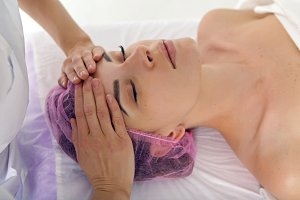 massage therapist cosmetologist doing massage of the shoulders, the girl lying