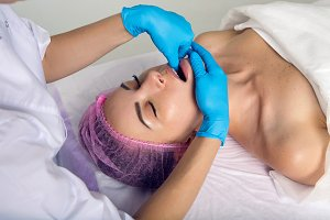 cosmetologist makes a buccal massage
