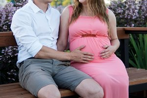 Married pregnant couple resting in the Park
