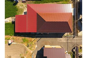 A house with a canopy over the courtyard. Roof from corrugated metal profile. Metal tiles.
