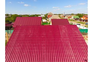 A house with a red roof made of corrugated metal sheets. Roof from corrugated metal profile. Metal tiles.