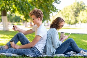 A young couple. Summer in nature. A boy with a girl resting on a plaid. Holds hot coffee or tea. They look at smartphones. Write messages on social networks.