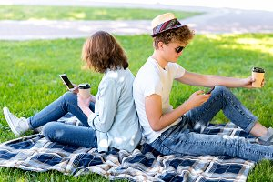 A guy with a girl in summer relax in nature. He holds a smartphone in his hands and reads correspondence. He holds a glass of coffee or tea in his hands. Enjoys relaxing on a plaid.