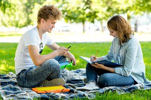 Students and schoolchildren in summer in the park. Girl and boy doing homework. In her hands holds a smartphone and a large notebook. Communicates makes notes in notepad.
