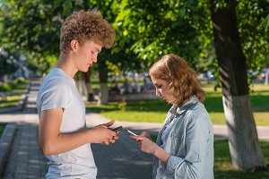 The boy and girl are facing each other. Summer in nature. In his hands holds a smartphone. Writes the phone number. Emotion dating in the park. . The guy gets acquainted with the girl.