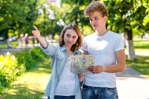 The girl shows the man direction of movement. Summer in nature. The passer-by shows where to go to the tourist. Young couple walking in the park in hands holding a road map.