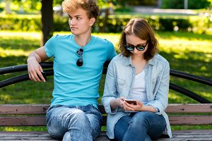 A guy with a girl in summer in a park in nature. They sit on a bench. In the hands of a smartphone is reading a social network. Rest of students in nature.