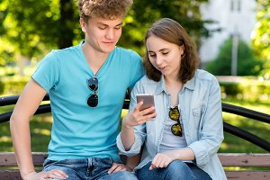 A guy and girl are sitting on a bench. Summer in nature. Girl in hands holding a smartphone. Emotionally smiling reads a social network.