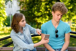 Guy with girl on nature. A woman is pointing at smartphone. Guy looks at correspondence with astonishment. Concept of betrayal betrayal of a young couple in summer. The problem is in relationship.