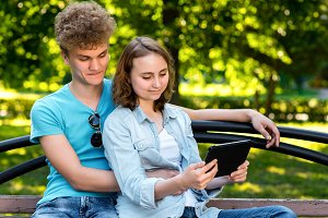 Young students in summer in a park outdoors. They sit on a bench in city. The guy is hugging the girl. Girl in hands holding a tablet. Smiling happily watching video on the Internet.