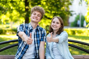 Young couple girl and boy. Summer in park on a bench. Smiles happily. Hard hands showing thumbs up, like. Emotionally gestures. The concept of success and success.