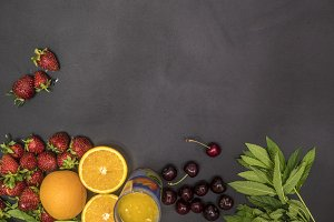 flat lay of fresh healthy food with mint cherry and orange juice copy space on blackboard