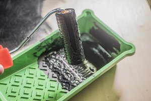 small roller paint in black color over the green plastic tray