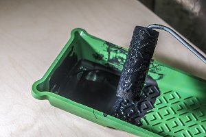 close up hand put roller tool in black colour paint in green tray in workshop