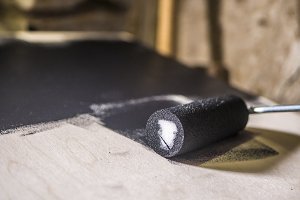 close up paint roller on the wooden surface, painting with black colour